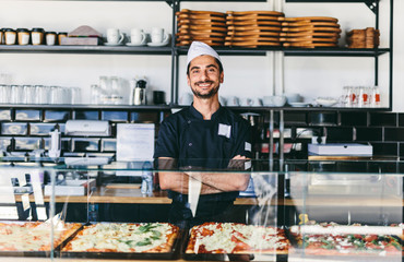 Portrait of smiling chef standing in pizzeria