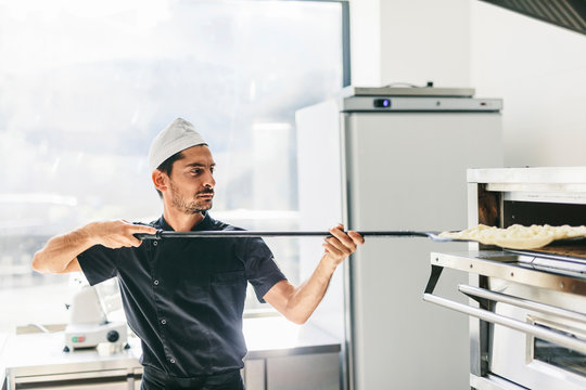 Chef inserting pizza in oven at kitchen