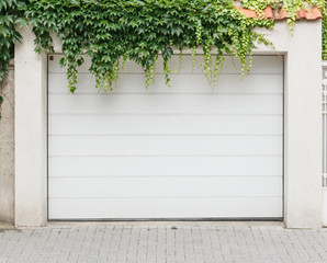 White closed wooden single garage doors in front covered with green ivy foliage. Grey tiles near.