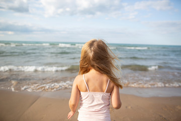 Rear view of girl standing on shore at beach against sky