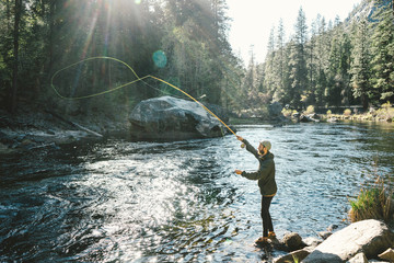 Side view of man Fly-fishing while standing on rock in river at Yosemite National Park