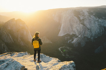 High angle view of female hiker standing on cliff at Yosemite National Park