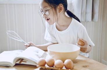 Smiling girl looking at cookbook while preparing food in kitchen