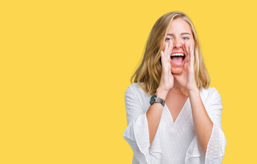 Beautiful young elegant woman over isolated background Shouting angry out loud with hands over mouth