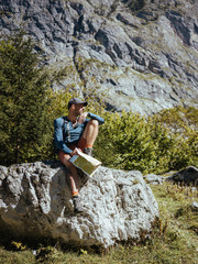 Full length of hiker with map sitting on rock against mountain in forest during sunny day