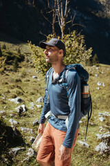 Hiker with backpack and map looking away while standing in forest during sunny day
