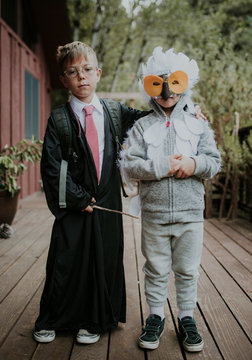 Full length portrait of brothers dressed up as Harry Potter and owl on floorboard during Halloween