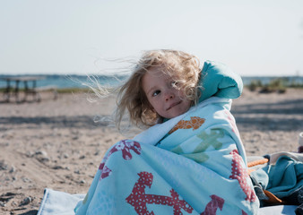 Cute girl with messy hair looking away while sitting at beach