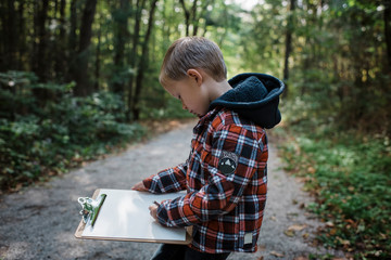 Side view of boy writing in paper on clipboard while standing at forest