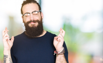 Young hipster man with long hair and beard wearing glasses smiling crossing fingers with hope and eyes closed. Luck and superstitious concept.