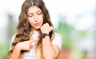 Young beautiful woman wearing casual white t-shirt In hurry pointing to watch time, impatience, upset and angry for deadline delay
