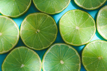 Top view of  green fresh slices of lime on turquoise or blue background in natural lights with shadows. Summer refreshment