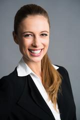 attraktive Geschäftsfrau vor grauem Hintergrund