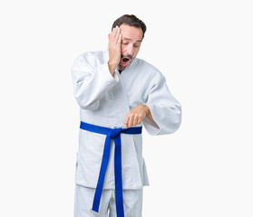 Handsome middle age senior man wearing kimono uniform over isolated background Looking at the watch time worried, afraid of getting late