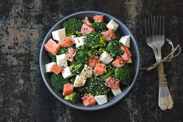 Colorful healthy salad with broccoli, white cheese and salmon. Keto diet.