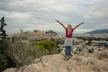 travel girl back to camera in freedom pose with hand up on top of rock with Acropolis world heritage touristic site in Athens city - capital of Greece