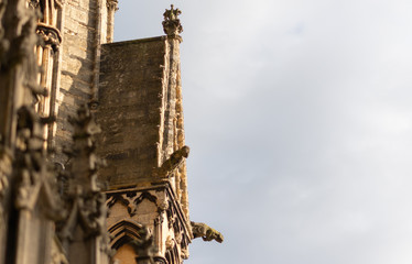 A close up shot of some of the details, statues and roofing of the Lincoln Cathedral against a overcast sky Fotobehang