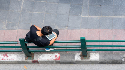 top view of man uses personal smart tablet and stands at outdoor pedestrian street
