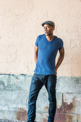 Young African American Man in New York, wearing blue V neck T shirt, flat cap, black pants, shrugging shoulders, arms backward down, hands on back, standing by painted wall on street, frowned, looking