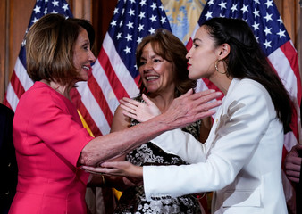 Rep. Alexandria Ocasio-Cortez (D-NY) greets Speaker of the House Nancy Pelosi (D-CA) before a ceremonial swearing-in picture on Capitol Hill in Washington