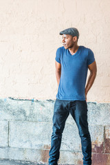 Young African American Man in New York, wearing blue V neck T shirt, flat cap, black pants, shrugging shoulders, arms backward down, hands on back, standing by painted wall on street, looking away...