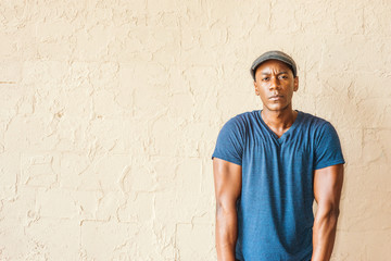 Portrait of Young African American Man in New York. A black guy wearing blue V neck T shirt, flat cap, straightening arms, shrugging shoulders, standing by painted wall on street, looking, thinking.
