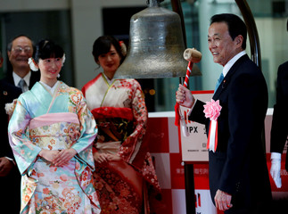 Japan's Deputy Prime Minister and Finance Minister Taro Aso poses as he prepares to ring a bell during the New Year opening ceremony at the Tokyo Stock Exchange (TSE), held to wish for the success of Japan's stock market, in Tokyo