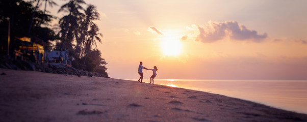 Beautiful young couple in love whirls holding hands on the beach at sunset during the honeymoon vacation travel