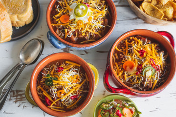 Chilli in three colorful bowls topped with cheese