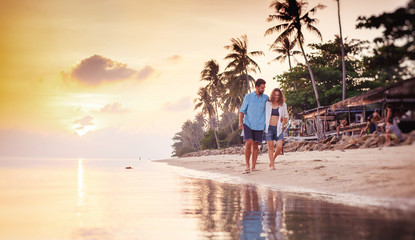 Beautiful young love happy couple walking arm in arm on the beach at sunset during the honeymoon vacation travel