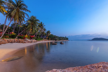 Fototapete - Bright colorful sunset on the tropical sea, long exposure shot, blurred water. Palm trees and sandy beach