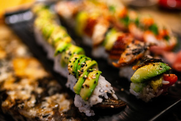 Sushi Rolls at restaurant. Luxury sushis with avocado and eel topping, rainbow maki, tuna, tobiko, sesame seeds. Japanese food.