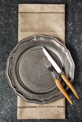 Vintage empty plate and fork and knife with napkin on dark grey stone background.