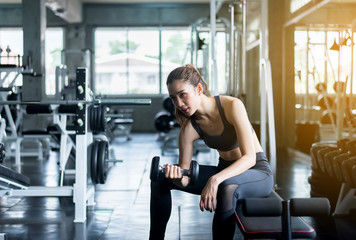 Sporty woman exercise with dumbbells,Female in sportswear does the exercises at gym