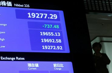A man is seen behind an electronic board showing the Nikkei average after the New Year opening ceremony at the Tokyo Stock Exchange (TSE), held to wish for the success of Japan's stock market, in Tokyo