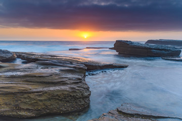 An Atmospheric Sunrise Seascape with Large Rocks