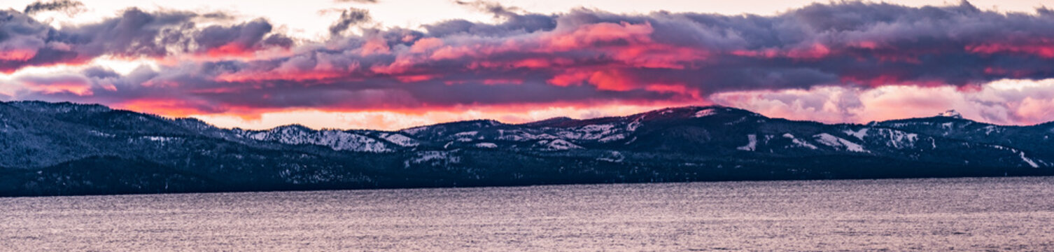 Beautiful sunset views of Lake Tahoe, Sierra mountains covered in snow vizible in the background; California