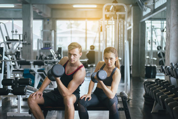 Sporty man and woman exercise with dumbbells,Couple sport people in sportswear does the exercises at gym