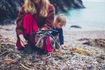 Young mother and toddler cleaning up rubbish on beach