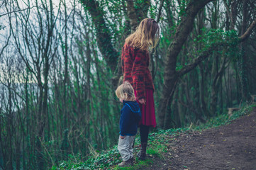 Young mother and toddler walking in the woods
