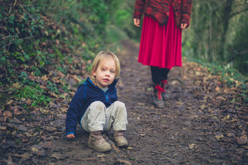 Toddler sitting on path in woods wtih mother behind him