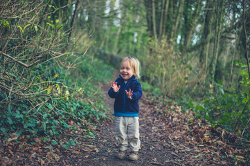 Little toddler standing on path in the woods