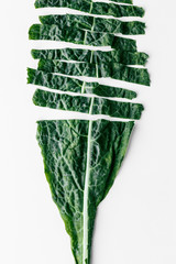 Sliced of a fresh organic green kale leaf on a white background, flat lay healthy nutrition concept