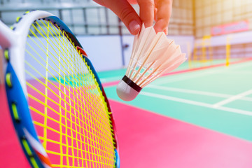 close up hand hold serve badminton shuttlecock with blur badminton court background