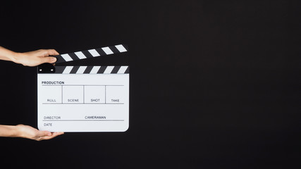Two Hand's holding white Clapperboard or Clap board or movie slate use in video production ,film, cinema industry on black background.