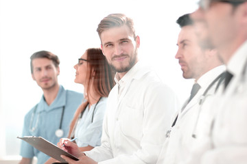 Close up of smiling doctor sitting with his team
