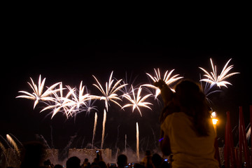 Viewers watch beautiful fireworks in the sky