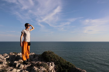 Woman looking over the sea into the distance
