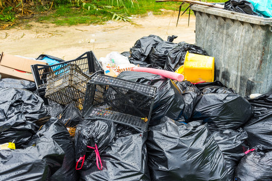 Junkyard of many plastic bags and other plastic trash in garden