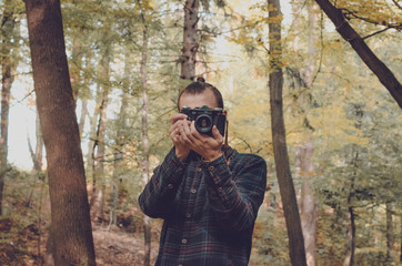 Hipster millennial young man or teenager with analog vintage photo camera makes photograph into lens in middle of old wood with sunset light, explores tourism. Hipster Travel Lifestyle concept